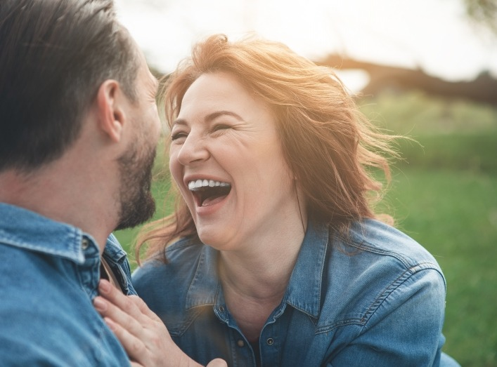 Man and woman laughing together after dental implant tooth replacement
