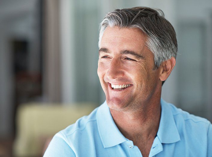 Man laughing with flawless smile after replacing missing teeth
