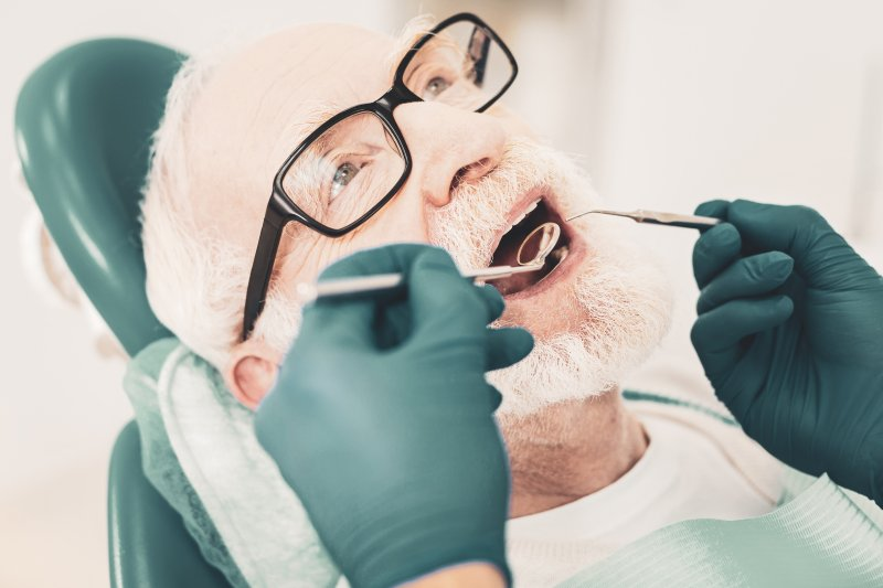 an elderly man having his teeth checked by a dentist during a six-month appointment